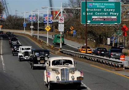 Motorcade of old cars carrying the Kennedy family.