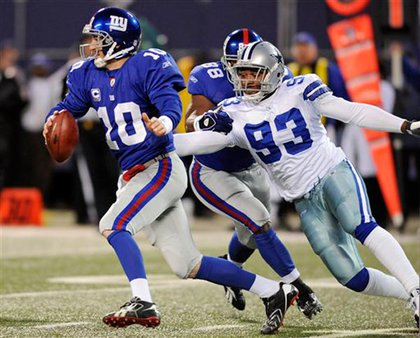 Giants quarterback Eli Manning scrambling away from Dallas Cowboys linebacker Anthony Spencer