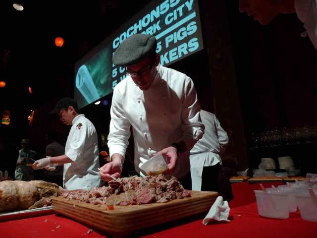Team Del Posto brushes up a giant butcher block topped with chopped pork.