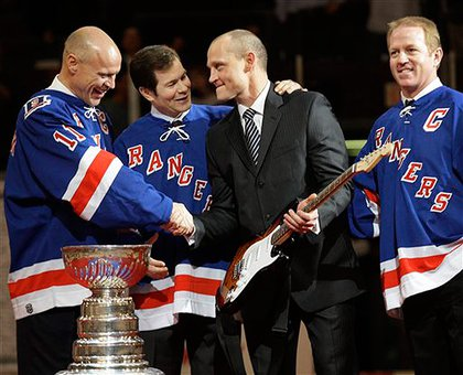 Graves shakes Messier's hand as Richter and Leetch look on.  He received a guitar autographed by Bruce Springsteen.