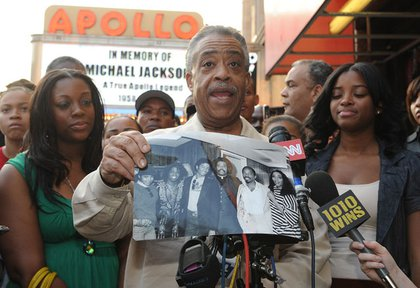 Rev. Al Sharpton holds a black and white photograph of himself and Michael Jackson outside the Apollo Theatre.