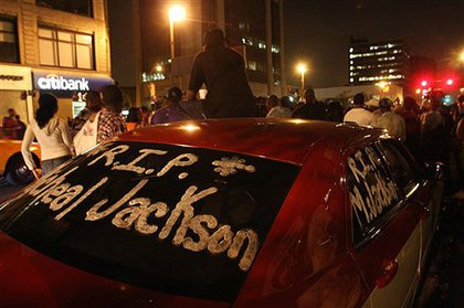 A driver puts a tribute on his car—in shoe polish—in Queens.