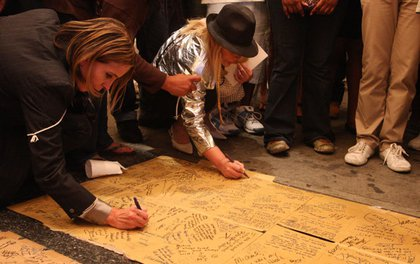 Dressed in tribute to Michael Jackson, Susana Kiara, second from left, writes a few words in tribute to Jackson outside the Apollo Theatre.