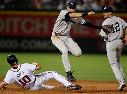 Derek Jeter forces out Atlanta Braves' Chipper Jones on a double play