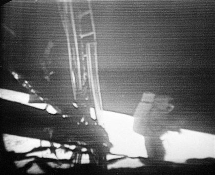Apollo 11 Commander Neil Armstrong walks slowly away from the lunar module to explore the surface of the moon.