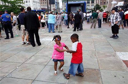 During the screening of Michael Jackson's memorial, two young children dance.