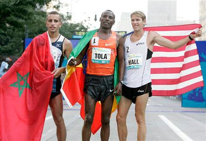 First place finisher Tadese Tola, of Ethiopia, , second place finisher Ridouane Harroufi, of Morocco, left, and third place Ryan Hall of the United States pose for a picture at the finish line of the New York City Half Marathon