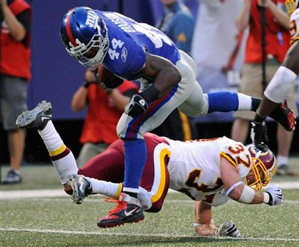 Running back Ahmad Bradshaw jumps over Washington Redskins safety Reed Doughty