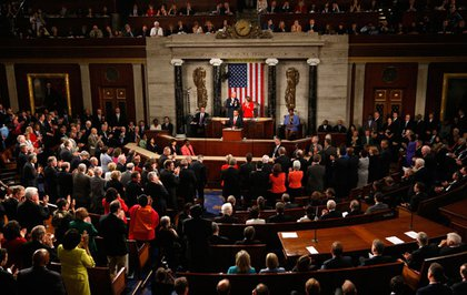 On the left, Democrats stand and applaud while, on the right, Republicans sit