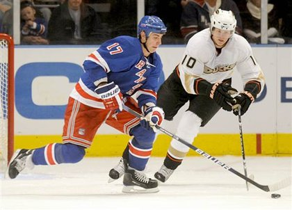 The Rangers' Brandon Dubinsky, left, and Anaheim Ducks' Corey Perry fight over a puck