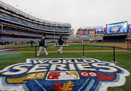 Eric Hinske and CC Sabathia walk the newly painted World Series logo on the field at Yankee Stadium.