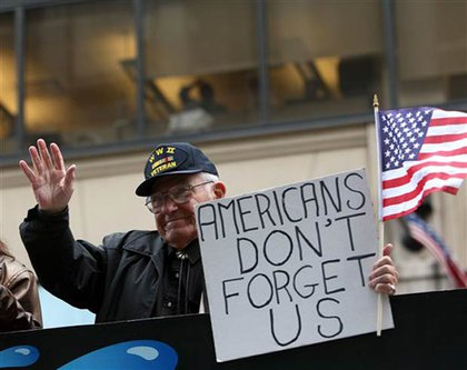 WWII veteran Rudy Castore holds up a sign