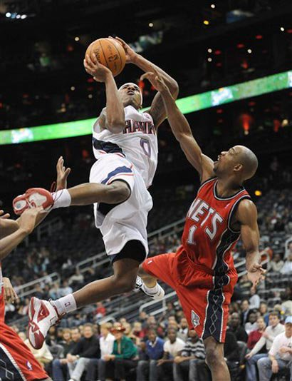Jeff Teague jumps over the Nets' Rafer Alston