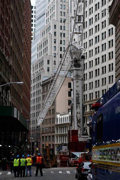 This morning, crews work to take down the crane on Maiden Lane.