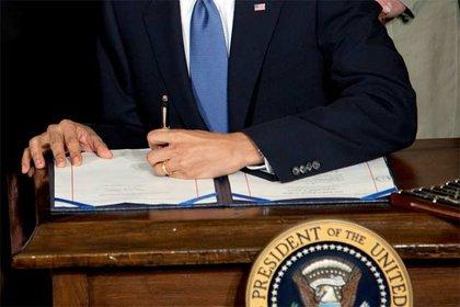 President Obama signs the health insurance reform bill