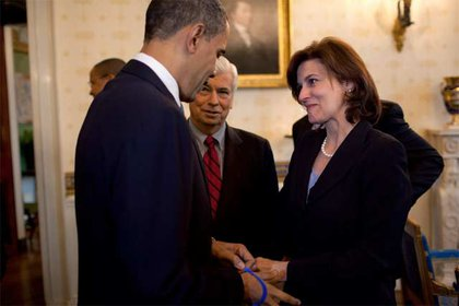 """Victoria Kennedy gives President Obama a """"Tedstrong"""" bracelet, with Senator Chris Dodd looking on."""