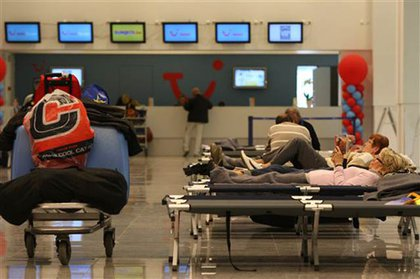 Travelers sleep in cots at the airport in Brussels