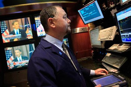 A trader listens to Obama's speech while working