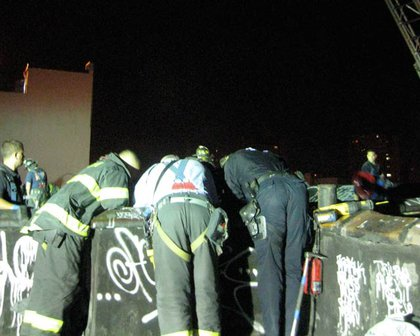 Firefighters peer down the shaft at 141 S 5th Street