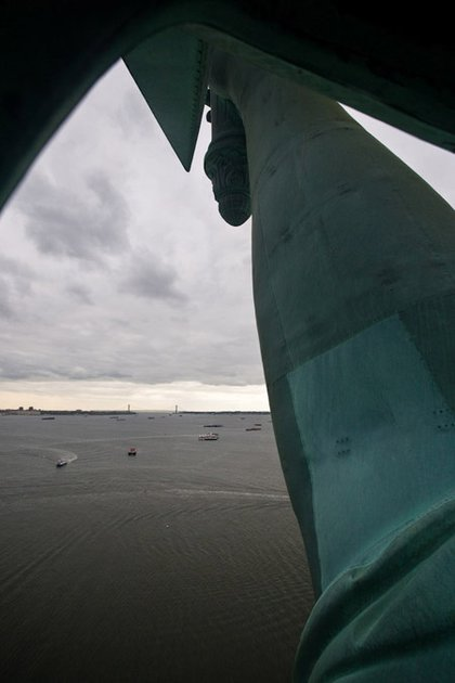 Looking right out of the crown with the statue's arm in the foreground and the Verazanno Bridge in the background.