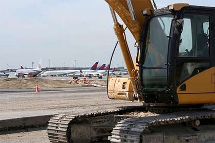 An excavator takes a rest adjacent to the newly paved Bay Runway.