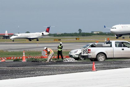 Construction workers dig a hole alongside a soon-to-be resurfaced taxiway.