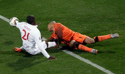 US keeper Tim Howard makes a save against Emile Heskey, but takes a shoe to the chest on the 50-50 ball.