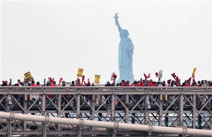 Protesters on the Brooklyn Bridge, with the Statue of Liberty in the background