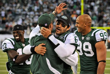 Mark Sanchez hugs offensive coordinator Brian Schottenheimer after the touchdown to Holmes.