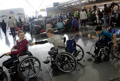 Some kids try out wheelchairs to pass the time at JFK