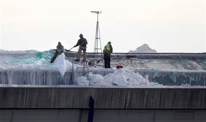 Workers clear snow from the roof of the Metrodome