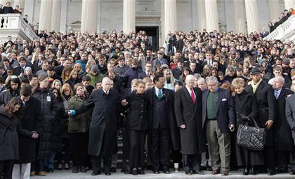 Members and staffers of Congress stand in a moment of silence on the steps of the Capitol.