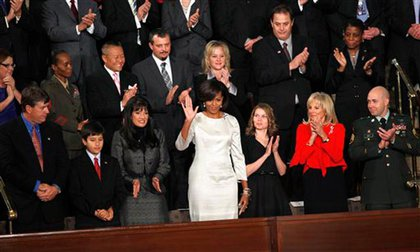 First Lady Michelle Obama waves; to her right are the parents and brother of 9-year-old Tucson shooting victim Christian Taylor Green