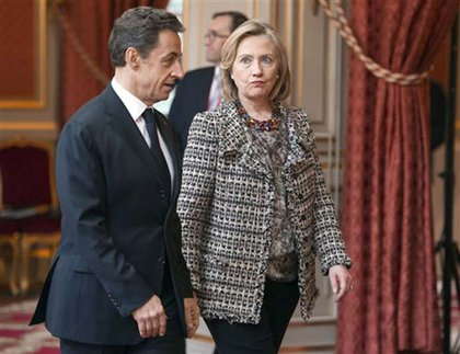U.S Secretary of state Hillary Clinton, right, and French President Nicolas Sarkozy walk in the Elysee Palace in Paris, during a crisis summit on Libya