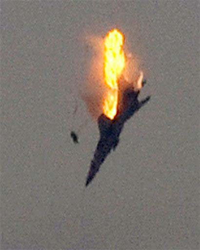 An object, thought to be the pilot, ejects from the cockpit of a doomed warplane after it was shot down by anti-Gadhafi forces over the outskirts of Benghazi, eastern Libya, Saturday, March 19, 2011