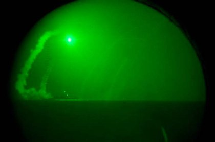 A  Saturday, March 19, 2011 photo provided by the U.S. Navy, seen through night-vision lenses aboard amphibious transport dock USS Ponce (LPD 15), the guided missile destroyer USS Barry (DDG 52) fires Tomahawk cruise missiles in support of Operation Odyssey Dawn from the Mediterranean Sea