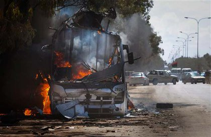 A bus burns on a road leading to the outskirts of Benghazi, eastern Libya