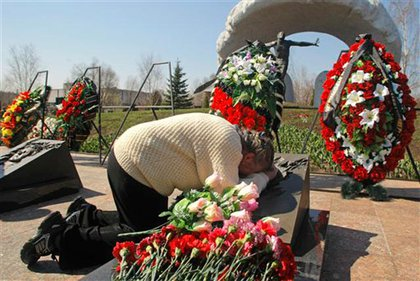 Vera Toptunova, the mother of Leonid Toptunov, who was a senior reactor control engineer at the Reactor No.4 of the Chernobyl nuclear plant when it exploded on April 26, 1986, mourns over his grave at Mitino cemetery in Moscow, Russia.