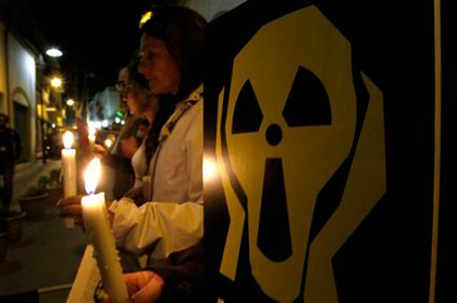 Greek and Turkish anti-nuclear activists hold candles and banners during a rally to mark the 25th anniversary of the Chernobyl nuclear accident at Ledras street at the U.N buffer zone in Nicosia, Cyprus.
