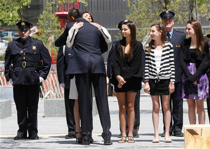 Obama hugs Diane Wall, whose husband Glen James Wall worked at the World Trade Center; to the right are Wall's two daughters
