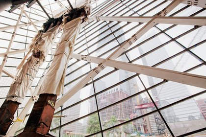 """Once inside the museum pavilion, you see these two enormous """"tridents"""" from the exterior base of the original World Trade Center buildings. In the distance you can see 1 WTC, which will eventually top out at 1776 feet (including the antenna)."""