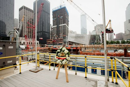 We've now walking behind the PATH Station and are looking South across the 9/11 Memorial Plaza to the Memorial Museum pavilion designed by Snøhetta, the Norwegian architecture firm.  4 WTC can be seen being built just above the memorial flowers.