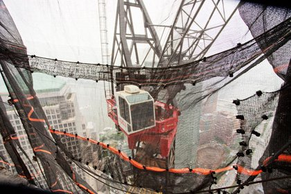 These cranes are cool: they can actually lift themselves up on a jack, while support is built beneath- so as the building advances up they go with it.  The driver sits in a glass-bottomed booth- not for the faint of heart.