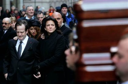Matthew Badger and Madonna Badger look on as a casket is being brought into the church.