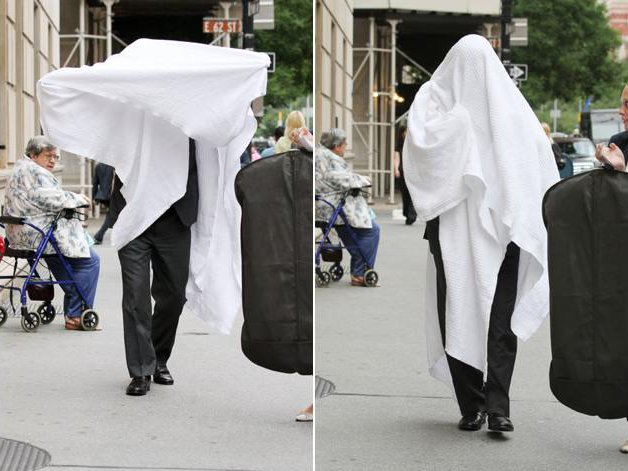 This is Alec Baldwin adjusting a white covering over his head on the Upper East Side today