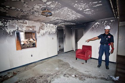 Sean Johnson, from the FDNY's Incident Management Team, shows the interior of a building where a basement fire was set the day before. The fire was directly under the kitchen, consuming its floor/the basement ceiling at around 1500 degrees.