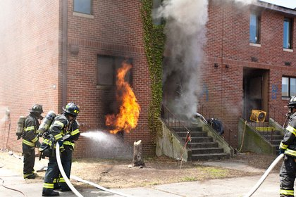 Firefighters start to put water on the basement fire during the live burn experiment at Governors Island