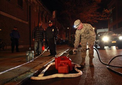 A National Guardsman fills gas for a person in Brooklyn