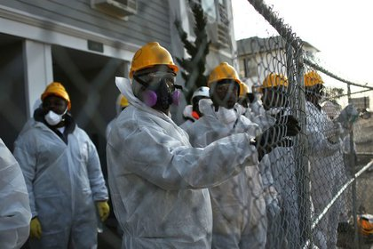 FEMA workers pause while cleaning homes on Saturday