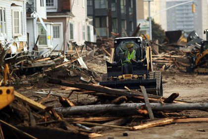 Crews tackle piles of debris on Saturday, November 10, 2012 as clean-up continues where a large section of the iconic boardwalk was washed away.